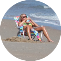 Woman sunbathing down by the ocean at South Beach.