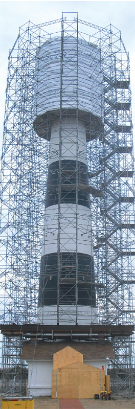 The Bodie Island Lighthouse is surrounded by scafolding, and the lightroom and balcony are enveloped in a wrap to protect them during restoration.
