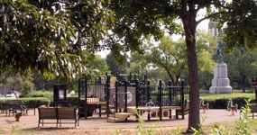 Playground equipment in Stanton Park, with the statue of General Nathanael Greene in the background.