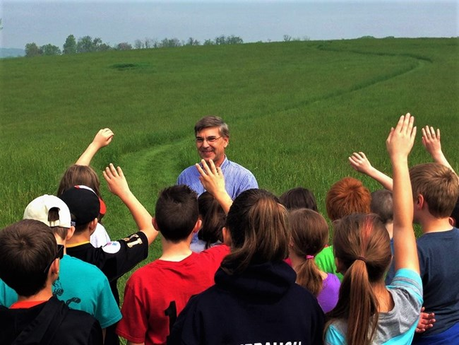 Staffer with a group of kids on a lush green field.