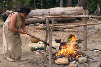 An interpreter cooks over an open fire at a recreated Woodland Indian village