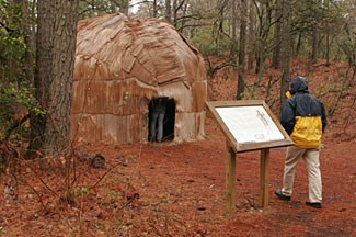 A visitor inspects a 17th century recreation of a Native American house
