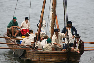 Historical reenactors row a replica of a shallop.