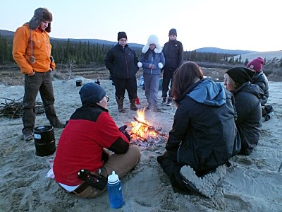 campers in warm clothes stand around a campfire