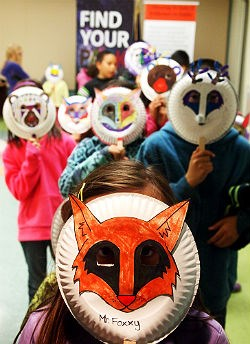 children in paper masks in a line