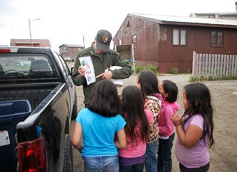park ranger teaches children on the side of the road