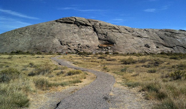 A hardened pathway leads through sagebrush to a large rounded grey rock formation with people in the distance.