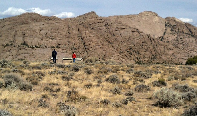 Two people stand in front of an outdoor exhibit while looking at a large rock formation called Split Rock in Wyoming with sagebrush.