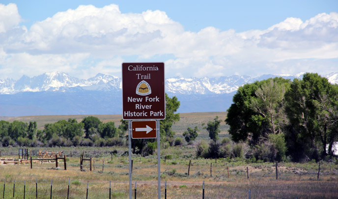 A brown directional highway sign with a yellow and white logo sits in front of cottonwood trees, and large snow covered gray mountains with clouds and blue sky