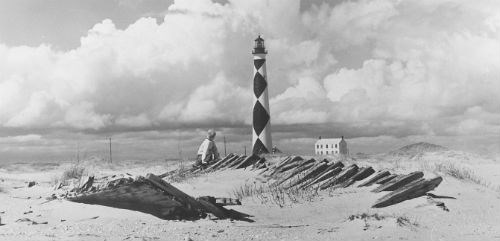 A boy plays in front of the Cape Lookout Lighthouse.