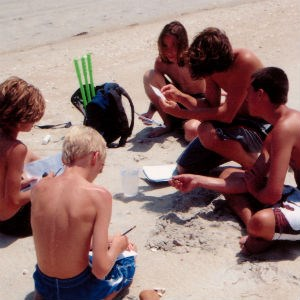 Boys work on their Junior Ranger Adventure booklets in the sand.
