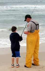 A ranger helps a young visitor to bait their hook for surf fishing.