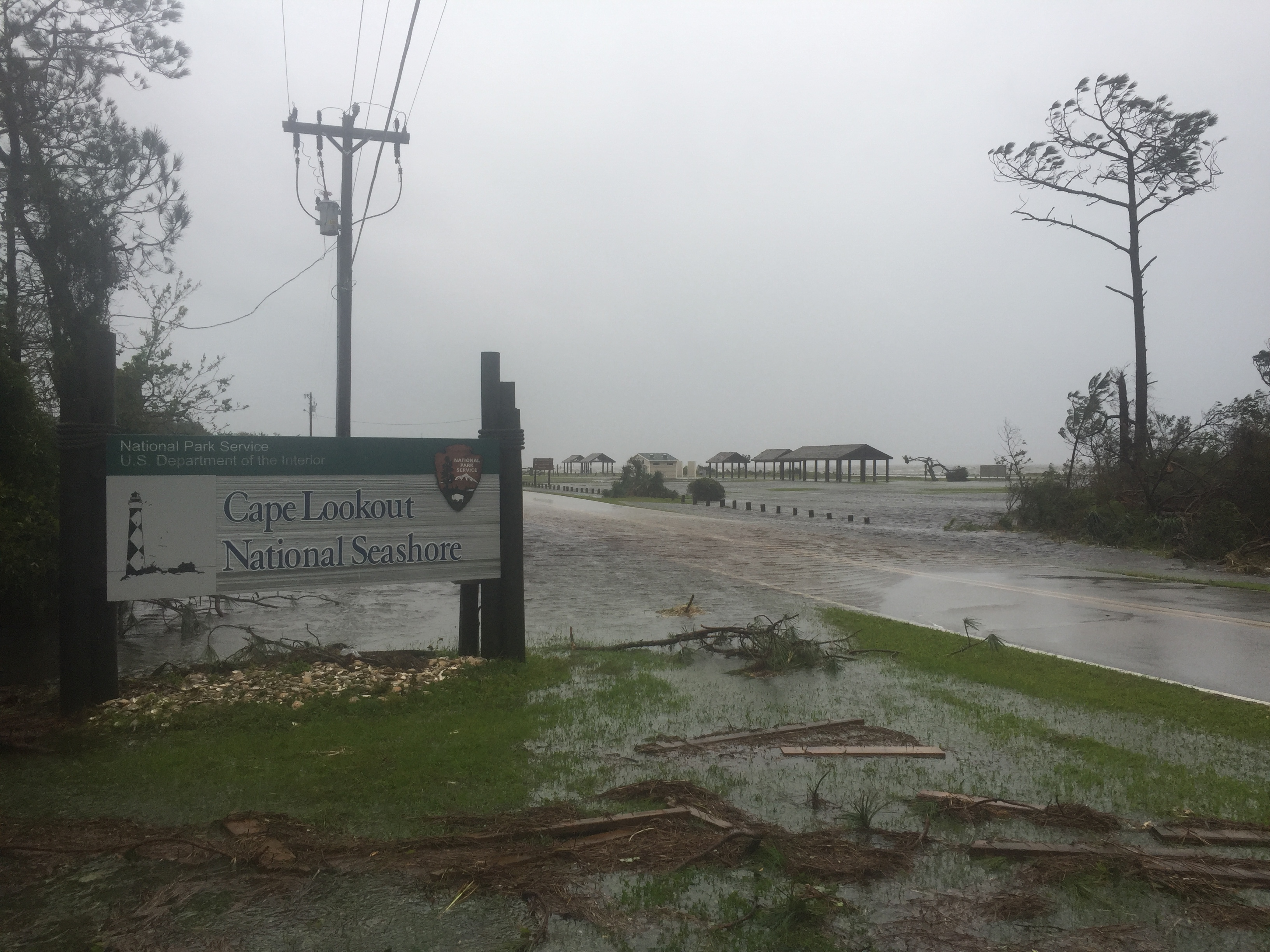 Flood waters and downed limbs surround the entrance sign for Cape Lookout National Seashore.