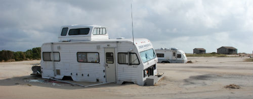 An RV buried to its wheels in sand after a hurricane.