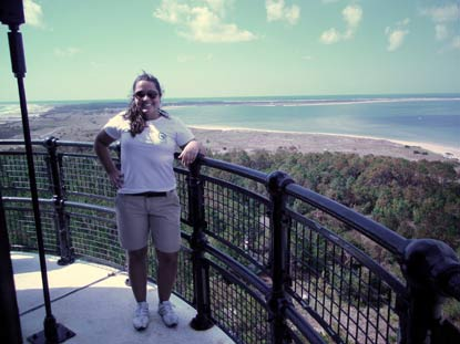 Jessica Vartanian on the gallery of the Cape Lookout Lighthouse with a view towards the point of Cape Lookout.