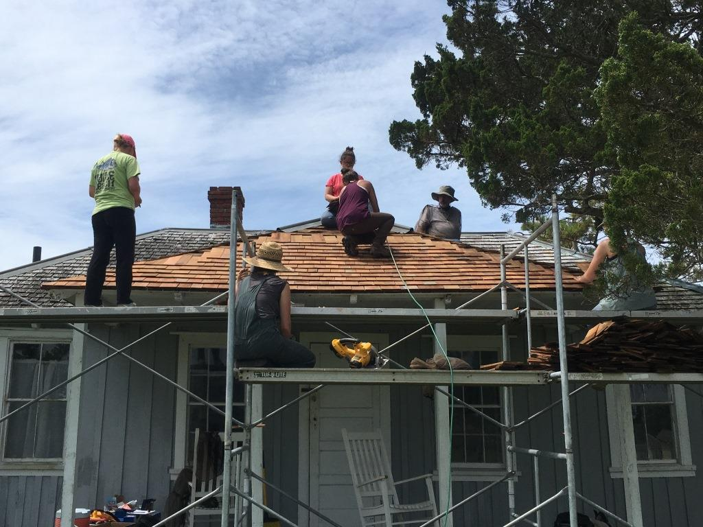 Six people work on the roof of an historic house