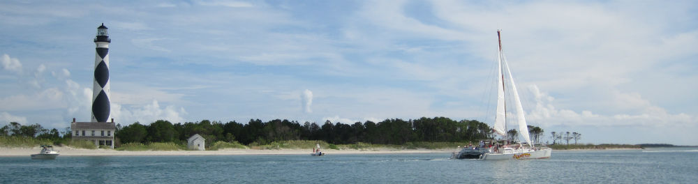 A sailboat in front of the Cape Lookout Lighthouse.