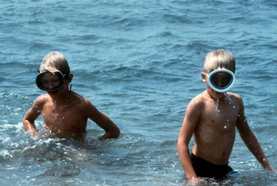 Two boys with face masks play in the water.