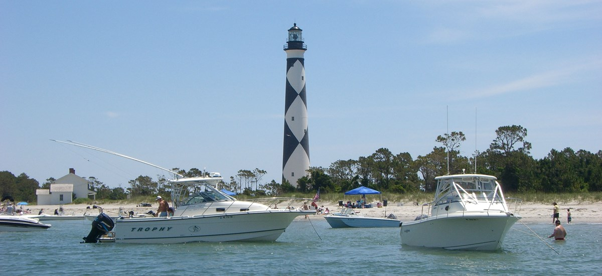 Boats drop anchor in front of the Cape Lookout Lighthouse.