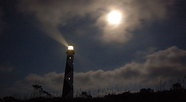 Cape Lookout Lighthouse at night with a moon in the sky and light showing from the lantern room at the top