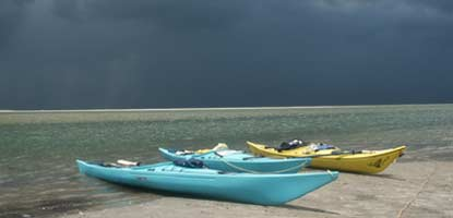 Storm clouds gather across the sound from a group of kayaks pulled up on the beach.