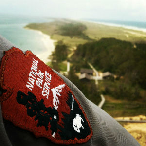 The National Patch Service patch on a ranger's shirtsleeve with the view from the top of the lighthouse in the background.