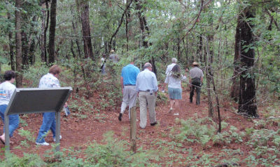 A group of visitors hike a trail.