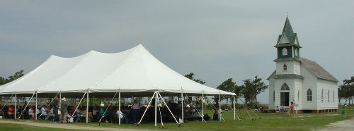 Visitors under a tent in front of the Portsmouth Village Church