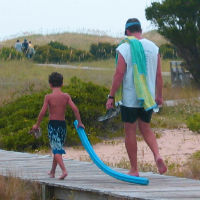 A man and boy walk along a boardwalk carrying beach toys.