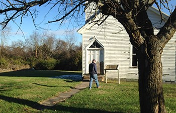 Man walks toward sign in front of old wooden church building