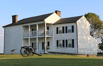 Two story wooden house with Civil War cannon in front
