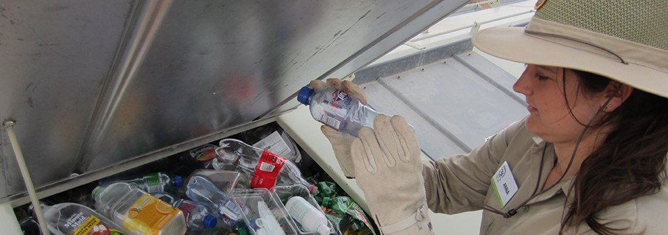 a woman puts plastic bottles into a recycling container