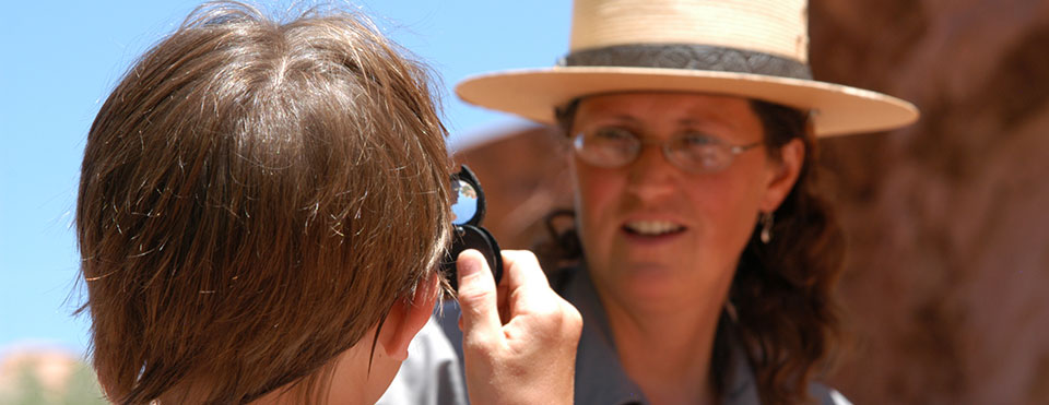 a student looks at a ranger through a magnifying lens