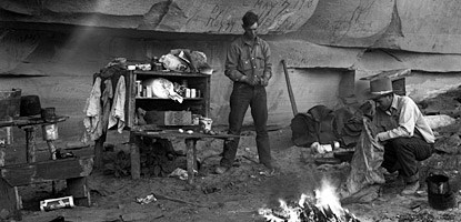 a cowboy stands among shelves and a campfire
