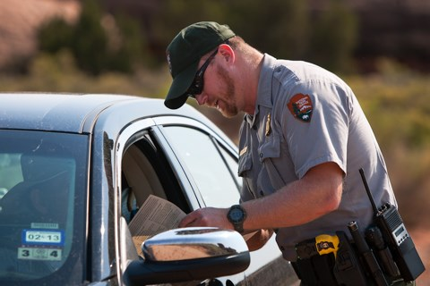 a park ranger talks with someone sitting in a car