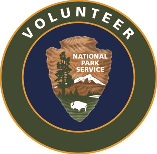 "a green circle surrounds the National Park Service arrowhead with the text ""Volunteer"""