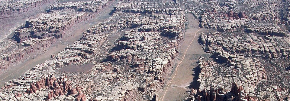 An aerial view of rocky cliffs with flat valleys in between