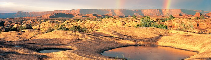 Natural stone basins with water, with rainbows in the distance