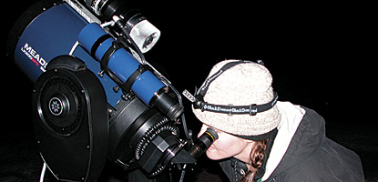 photo: Angie Richman calibrates a telescope for a monitoring session at Grand View Point.