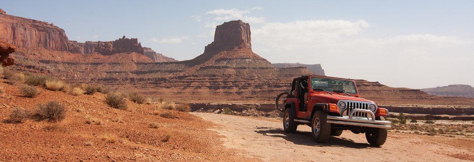 a red jeep drives a rock road in front of a tall rock tower