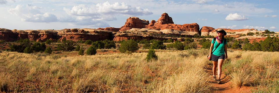 A woman hikes on a trail in front of red and white sandstone formations.