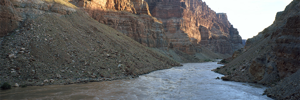 The Colorado River flows in a canyon with high cliffs.