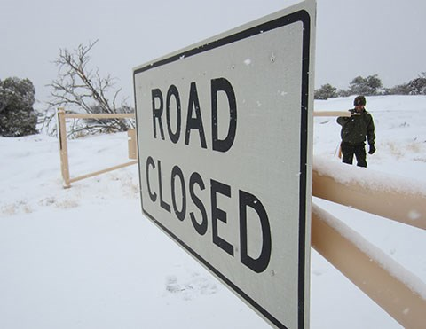 A road closed sign with snow in the background