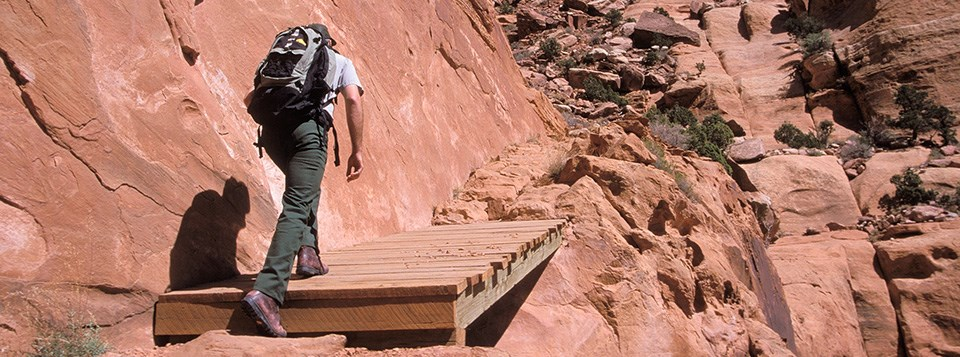 a man wearing a backpack hikes up a steep, rocky trail