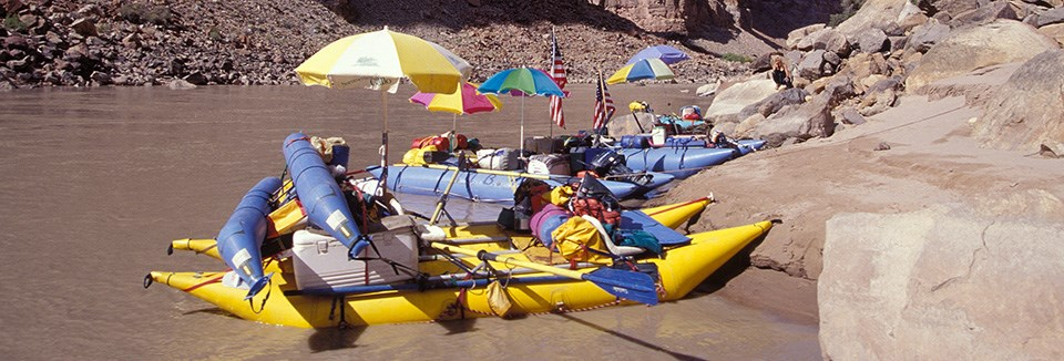 brightly colored rafts sit on the riverside