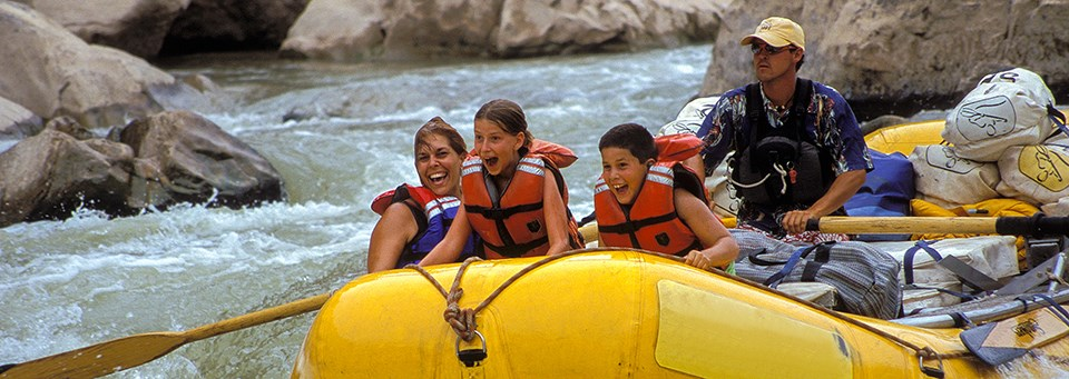 a family rides on river rapids in a yellow raft