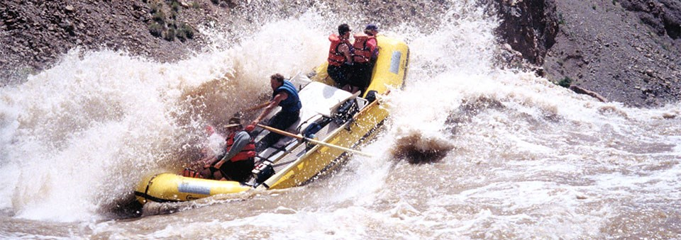a yellow raft passes through a whitewater section on a river