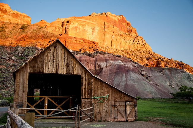 Large wooden barn with green pasture to the right of it and colorful red and gray striped cliffs above.