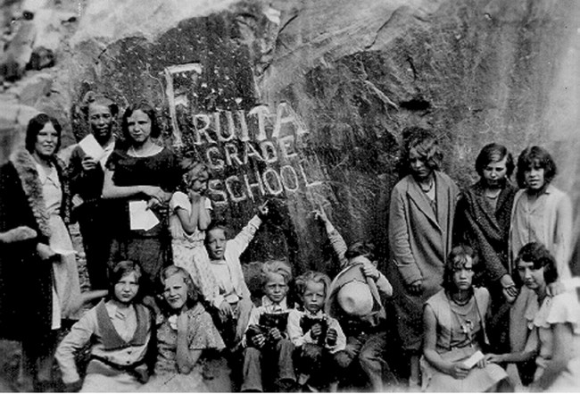 "Black and white photo of school children and adults beside a rock carved with ""Fruita Grade School"""