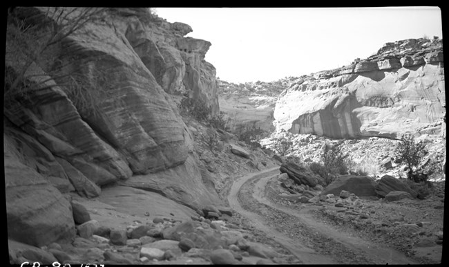 Black and white photo of narrow dirt road winding through narrow, rocky canyon.